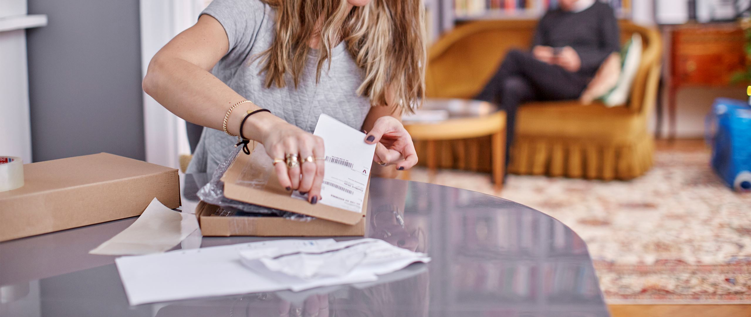 A girl attaching a shipping lable on a parcel.